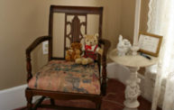 A dark red wood arm chair with a pink cushion rests in the corner in this tan and white room