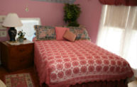 guestroom with rose colored walls, natrual sunllight through white sheers, intricate crochet rose colored bedspread