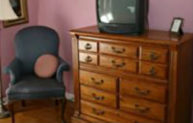 A blue arm chair sits in the corner beside a dresser in a pink guestroom