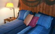 guest room with white walls, blue striped bedspread with blue, rose, and peach pillows