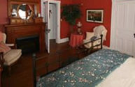 guest room with red painted walls, ceiling fan, black iron bed with blue floral window treatment and bed linens