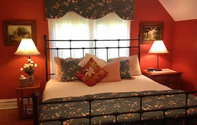 guest room with red painted walls,, black iron bed with blue floral window treatment and bed linens