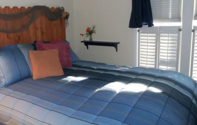 guest room with white walls, blue striped bedspread with blue, rose, and peach pillows, light coming through white shutters