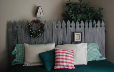 guest room with beige walls, rustic gray fence headboard with ficus tree behind, small wreach and photo on headboard, birdhouse on wall and green, white and red checked bed linens