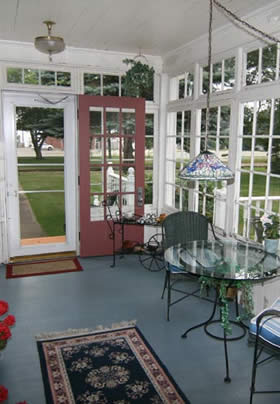 glass enclosed porch with red door, light hanging above glass and iron rod table and two chairs