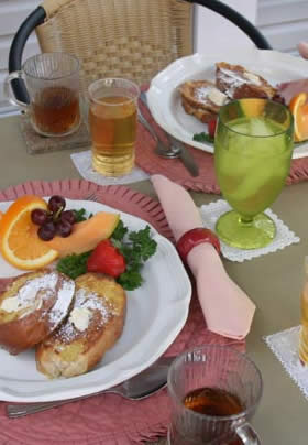 plated french toast and fruit medley on rose coored place mat, coffee in clear mug and apple juice in clear glass, with tinted green water glass on white napkin