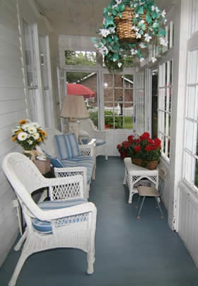 glass enclosed porch with white whicker couch and chair with blue stipped cussions facing the windows, flowering hanging basket hanging from the ceiling and red flowers on the white whicker coffee table